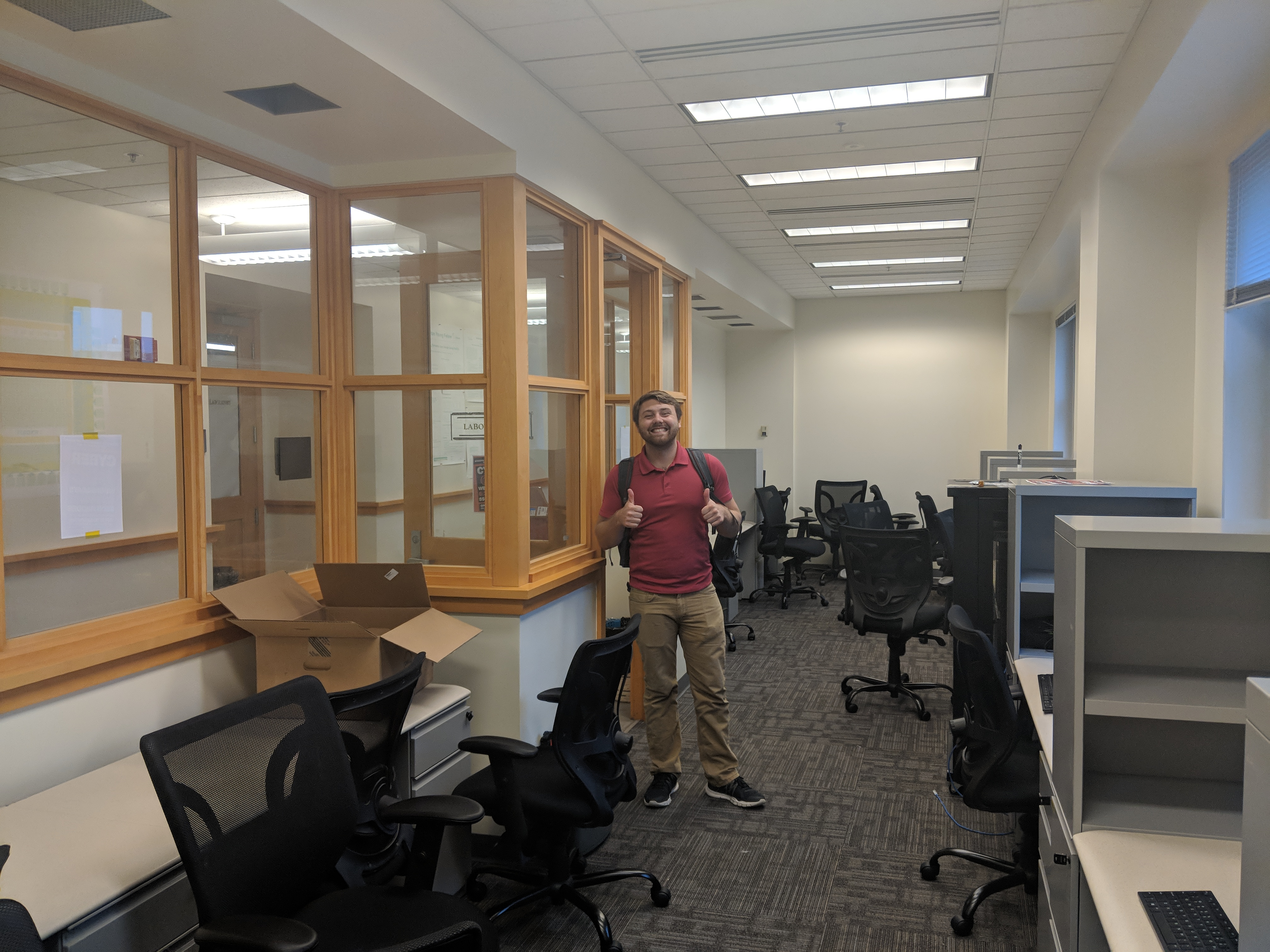 Ryan B. cheesing in the lab with our new desks
